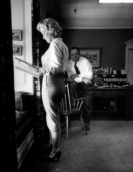 Bob Landry photographs Marilyn studying a script in producer Jerry Wald's office, 1951